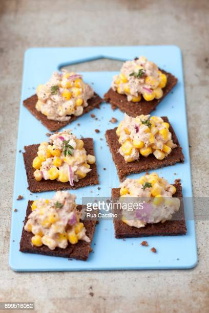 pumpernickel bread with tuna paste, sweetcorn and red onions - canap�� photos et images de collection