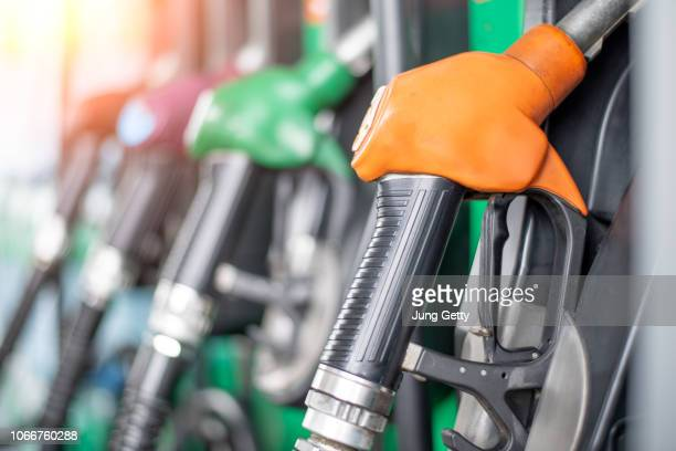 pumping equipment gas at gas station. close up of a hand holding fuel nozzle - distributore di benzina foto e immagini stock