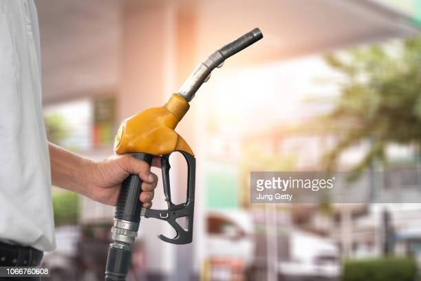 pumping equipment gas at gas station. close up of a hand holding fuel nozzle - estação imagens e fotografias de stock