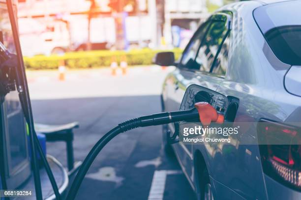pumping gasoline fuel in car at gas station - gas tank stock photos and pictures
