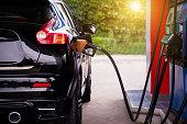 Pumping gasoline fuel in car.