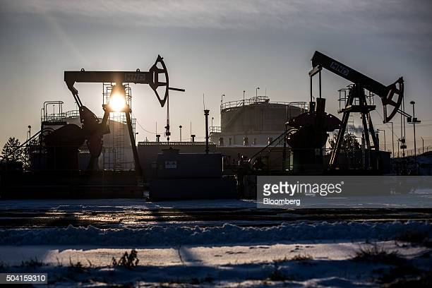 Pumping units also known as 'nodding donkey's' or pumping jacks stand silhouetted against the sun at an oil plant operated by Moravske Naftove Doly...