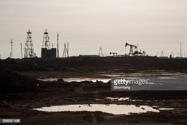 Pumpjack and drilling rigs stand in a field in Baku Azerbaijan on Sunday March 18 2018 Two years after descending into junk Azerbaijan's shortest...