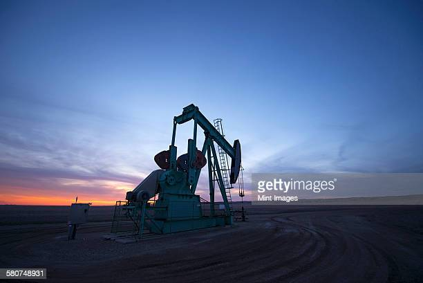 A pumpjack at an oil drilling site at sunset.