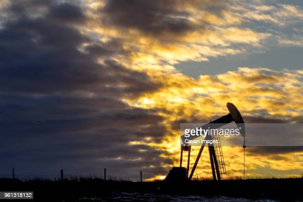 pumpjack at oil industry against cloudy sky during sunset - fracking stock pictures, royalty-free photos & images