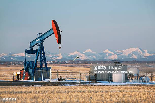 Pumpjack In A Field With Snow Covered Mountains And Blue Sky At Sunrise