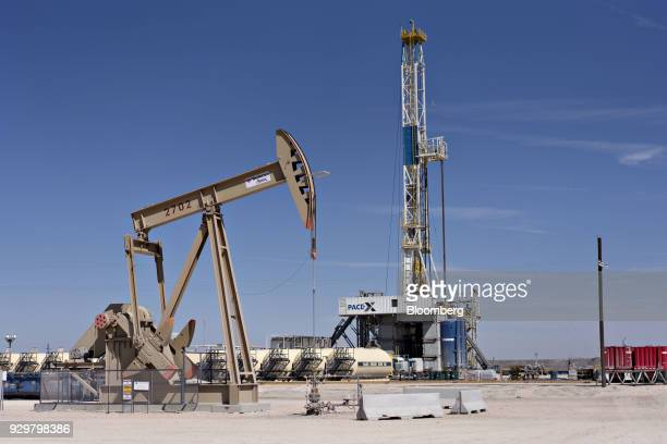 A pumpjack operates near a Nabors Industries Ltd drill rig standing over an oil well for Chevron Corp in the Permian Basin near Midland Texas US on...