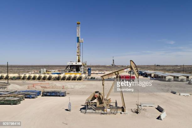 A pumpjack operates near a Nabors Industries Ltd drill rig standing over an oil well being drilled for Chevron Corp in the Permian Basin in this...