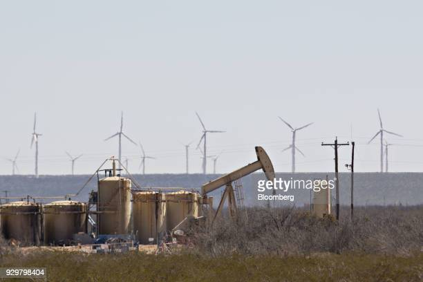 A pumpjack operating on an oil well as wind turbines stand in the Permian Basin near Crane Texas US on Friday March 2 2018 Chevron the world's...