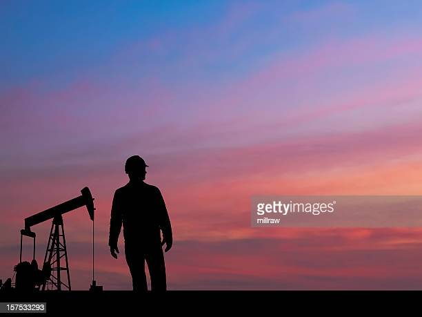 pumpjack silhouette with oil worker and pink sky - oil worker stock pictures, royalty-free photos & images