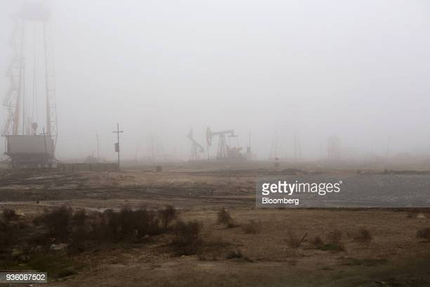 Pumpjacks and drilling rigs are shrouded in mist while operating in a field in Baku Azerbaijan on Sunday March 18 2018 Two years after descending...