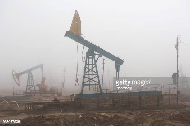 Pumpjacks are shrouded in mist while operating in a field in Baku Azerbaijan on Sunday March 18 2018 Two years after descending into junk...