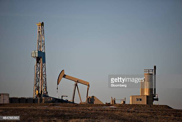 A pumpjacks operates in the foreground of a crude oil drilling rig outside Williston North Dakota US on Thursday Feb 12 2015 A plunge in global...