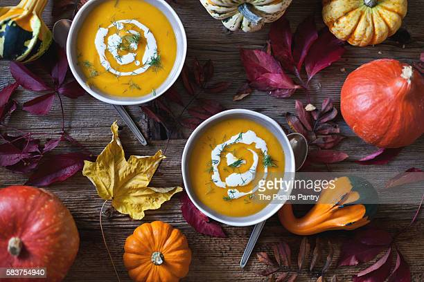 Pumpkin and sweet potatoes soup in bowls topped with cream and fresh dill