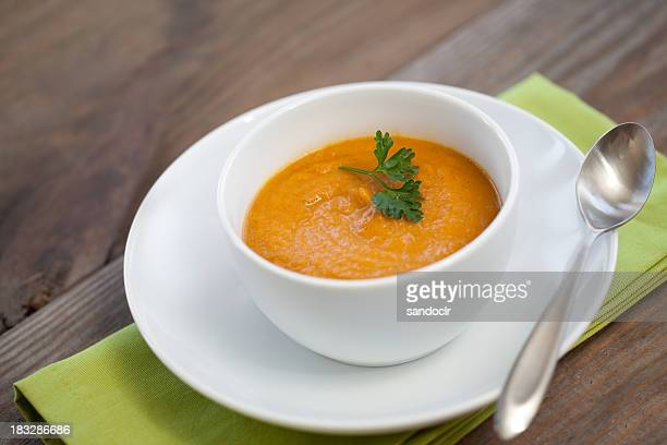 Pumpkin carrot soup in a white bowl with a green napkin