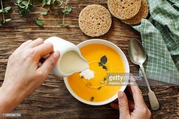pumpkin creamy soup on dark wooden background - soup stock pictures, royalty-free photos & images