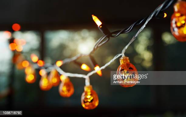 pumpkin electric light string against the window. halloween theme - happy halloween stock photos and pictures