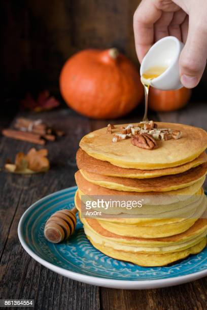 Pumpkin pancakes with honey and pecan nuts on a plate