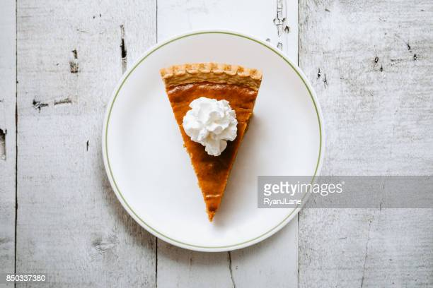 pumpkin pie slice on rustic background - whipped food stock pictures, royalty-free photos & images