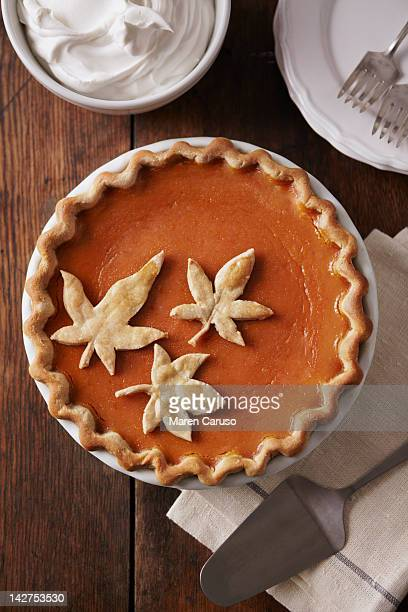 Pumpkin pie with leaf detail on wood table