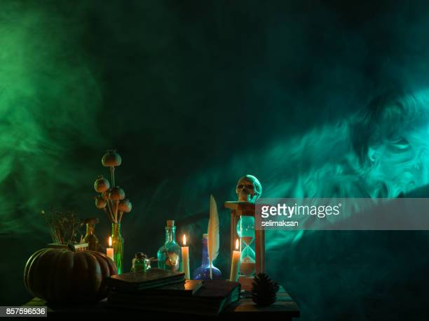 pumpkin, poison bottle, dead insects, candles, human skull and magic book for halloween - potion stock photos and pictures