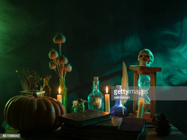 pumpkin, poison bottle, dead insects, candles, human skull and magic book for halloween - ceremony stock pictures, royalty-free photos & images