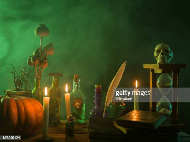 pumpkin, poison bottle, dead insects, candles, human skull and magic book for halloween - wizard stock pictures, royalty-free photos & images