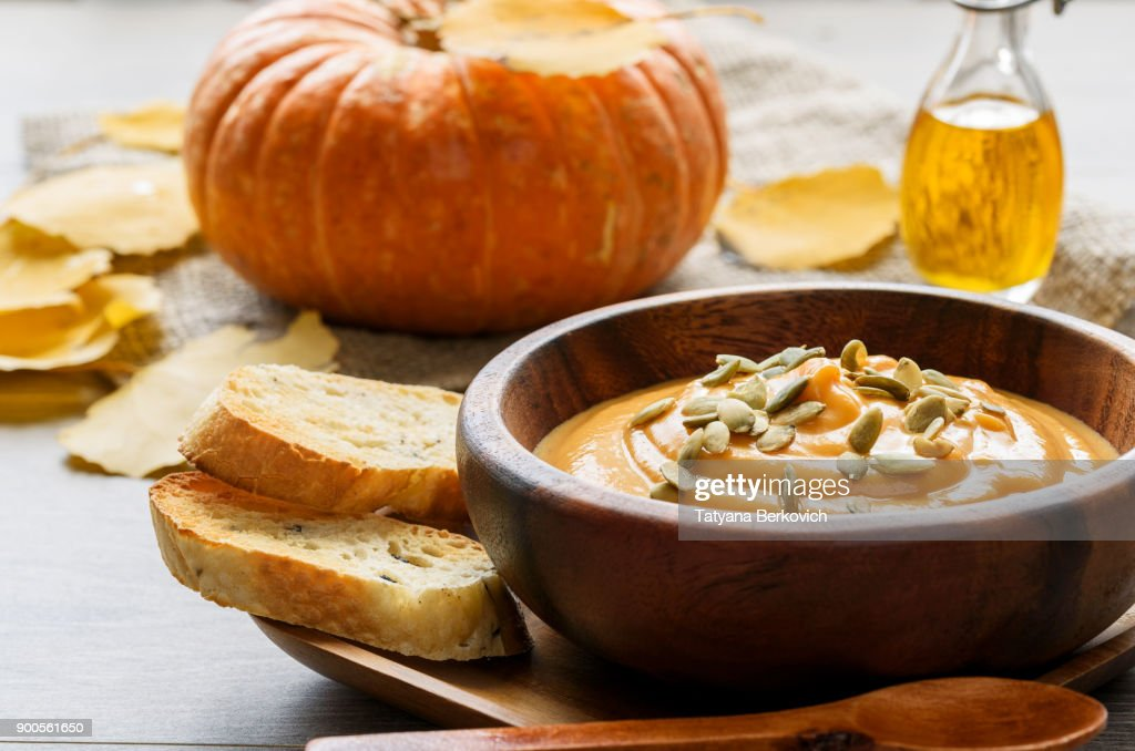 Pumpkin soup in a wooden bowl, with autumn leaves and pumpkin : Stock Photo