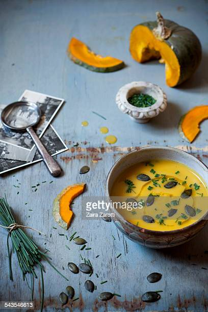 Pumpkin soup in bowl with seeds and chives