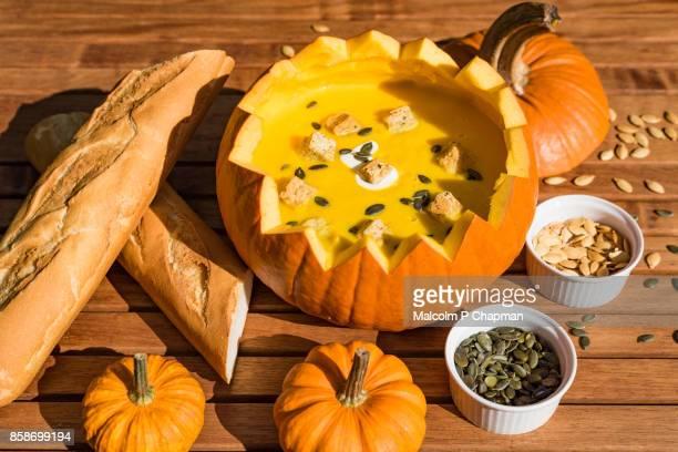 pumpkin soup in shell served with bread and roasted pumpkin seeds - halloween pumpkin - fotografias e filmes do acervo