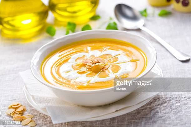Pumpkin soup in white dish with seeds and cream on top