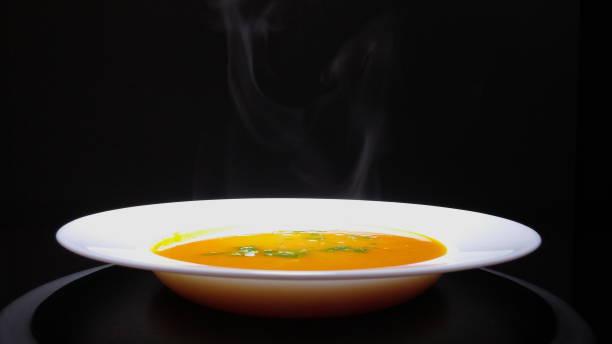 Pumpkin soup served in bowl on black background