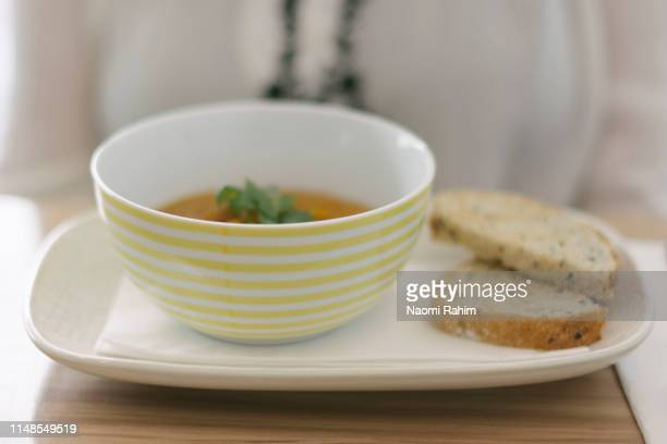 pumpkin soup served in striped bowl with bread - soup bowl stock pictures, royalty-free photos & images