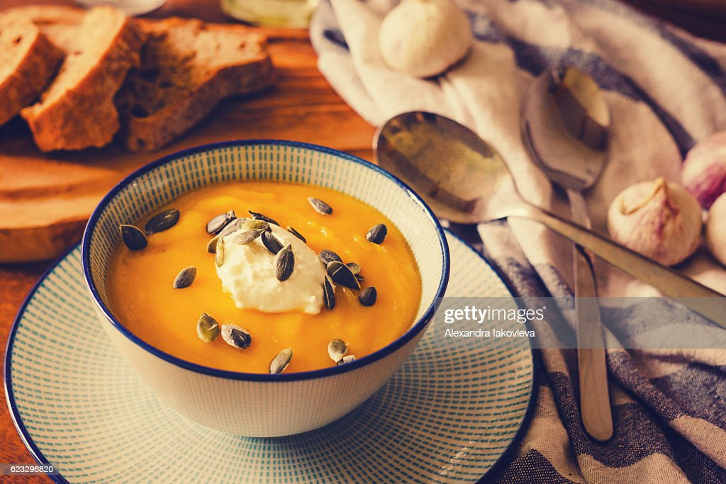 Pumpkin soup served with sour cream and pumpkin seeds : Stock Photo