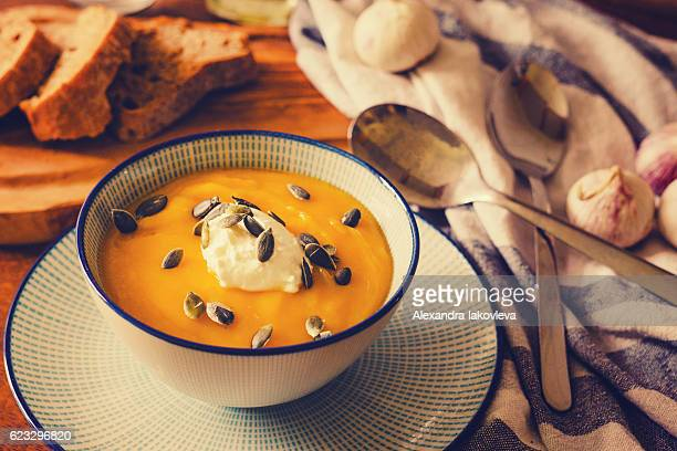 Pumpkin soup served with sour cream and pumpkin seeds