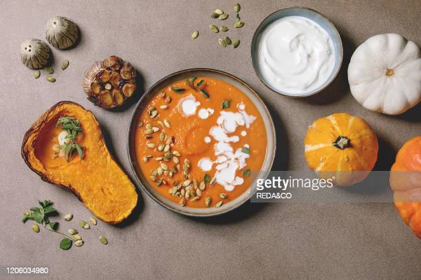 Pumpkin soup with cream and seeds in ceramic bowl, served with sour cream, baked and uncooked pumpkins and garlic over brown texture background. Flat...
