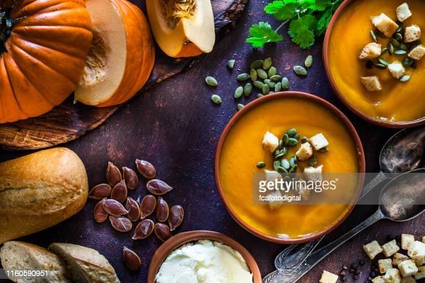 pompoensoep met ingrediënten op rustieke bruine tafel. top view - eetklaar stockfoto's en -beelden