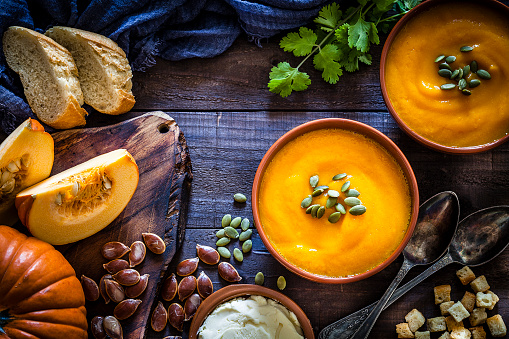 Pumpkin soup with ingredients on rustic wooden table 1062175262