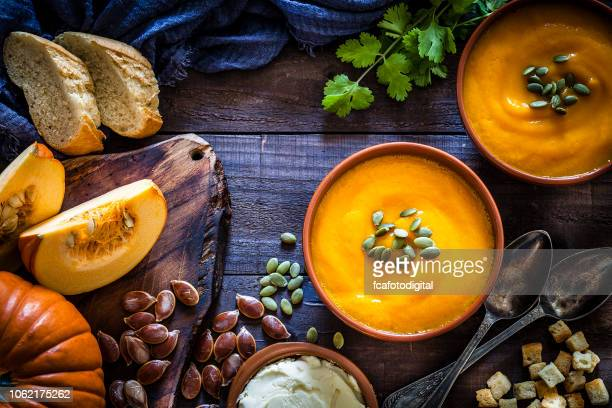 pumpkin soup with ingredients on rustic wooden table - food stock pictures, royalty-free photos & images