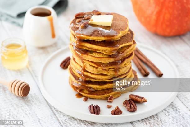 pumpkin spice pancakes stack on white plate - pancake stock pictures, royalty-free photos & images