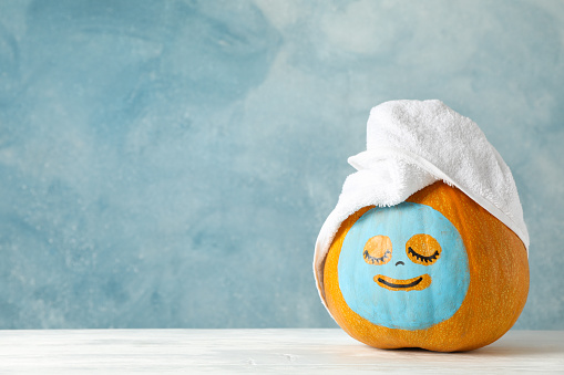 Pumpkin with facial mask and towel on wooden background, copy space 1178959163