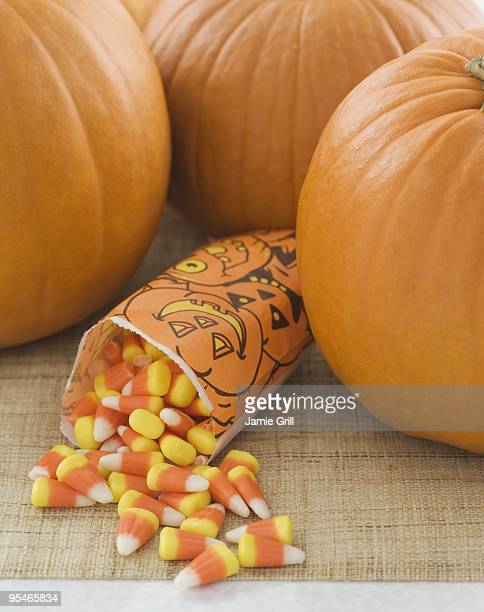 pumpkins and halloween candy - candy corn stock photos and pictures