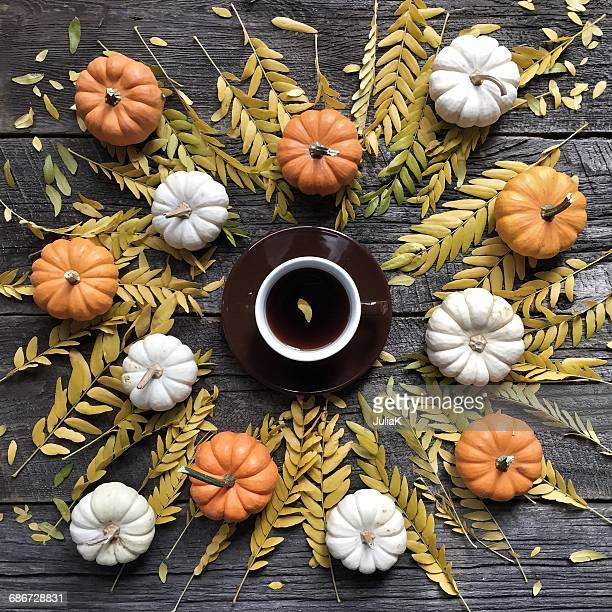 Pumpkins, autumn leaves and cup of coffee