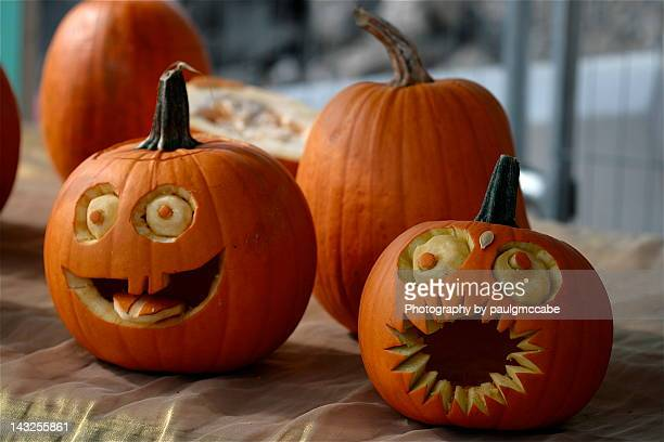 pumpkins decorated with faces with eyes and mouths - halloween lantern stock photos and pictures