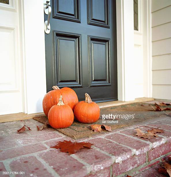 Pumpkins in front of door of house