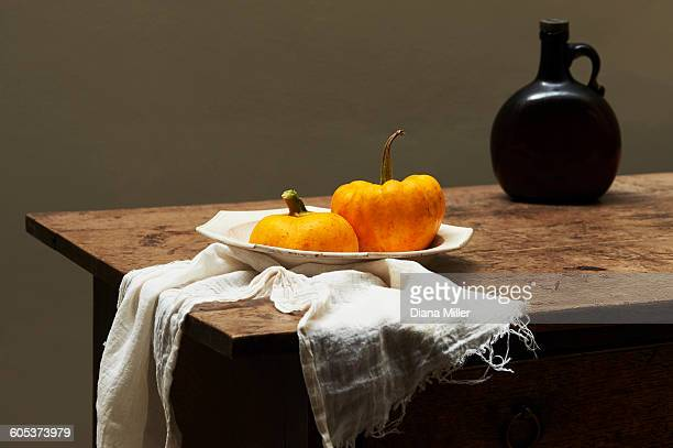 Pumpkins in serving dish on table with brown glass bottle