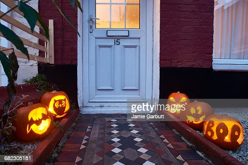 Pumpkins lining a path way to a house