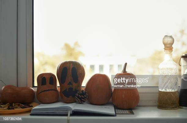 pumpkins painted for halloween on a window sill - arman zhenikeyev stock pictures, royalty-free photos & images