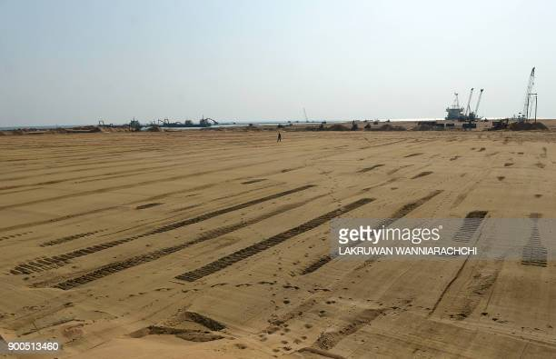 Pumps dredge sand to reclaim land at the site of a Chinesefunded $14 billion reclamation just next to Colombos main sea port on January 2 2018 China...