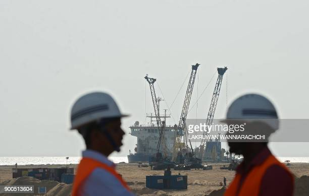 Pumps dredge sand to reclaim land at the site of a Chinesefunded $14 billion reclamation next to Colombo's main sea port on January 2 2018 China will...